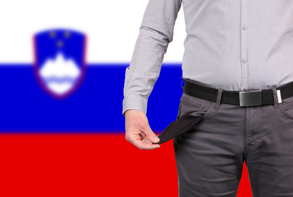 Businessman showing empty pockets over flag of Slovenia