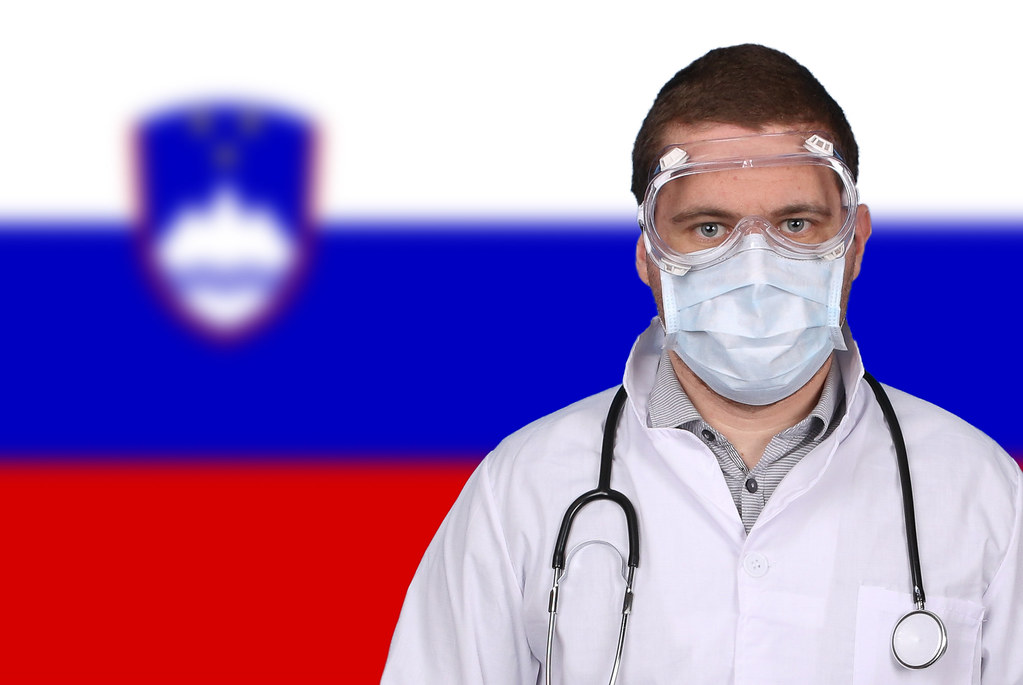 Doctor in protective medical mask over flag of Slovenia