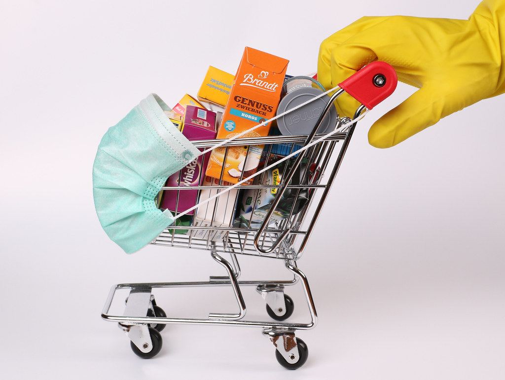 Hands in protective gloves pushing shopping cart with groceries and protective face mask corona virus or Covid-19 protection
