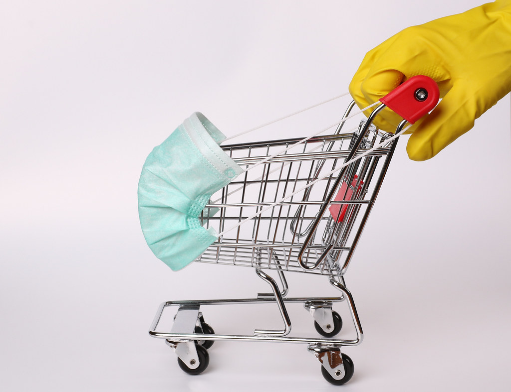 Hands in protective gloves pushing shopping cart with protective face mask corona virus or Covid-19 protection