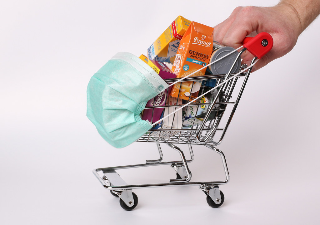 Hands pushing shopping cart with protective face mask corona virus or Covid-19 protection