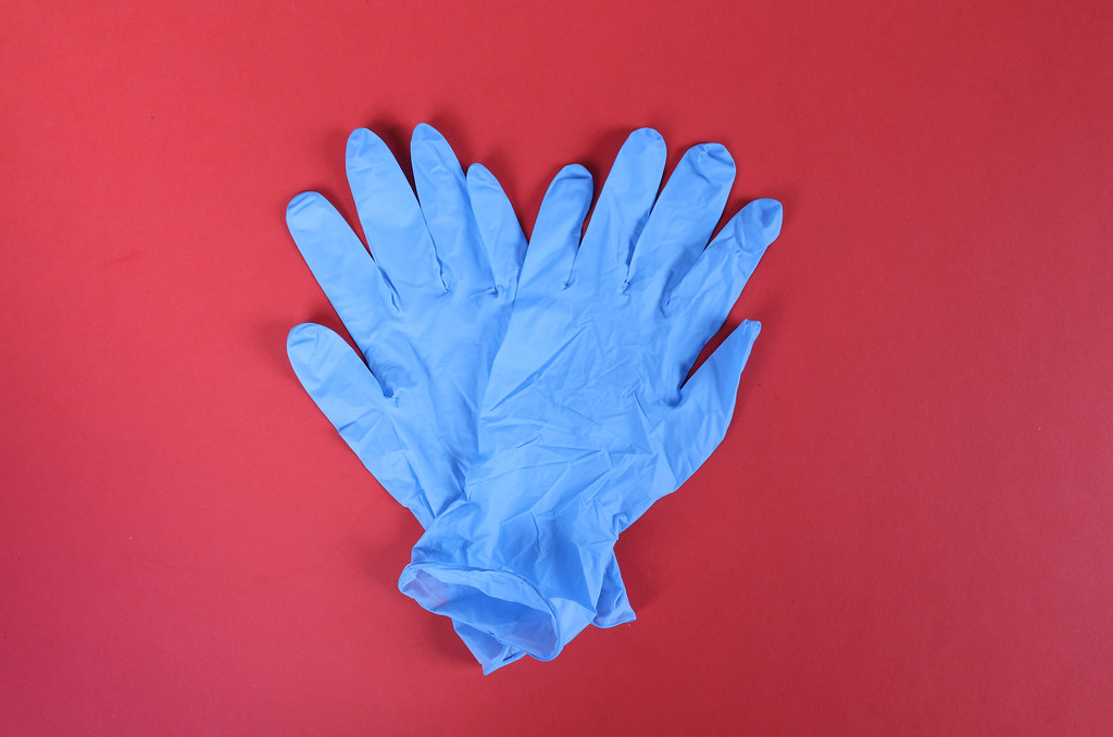 Protective gloves on red background