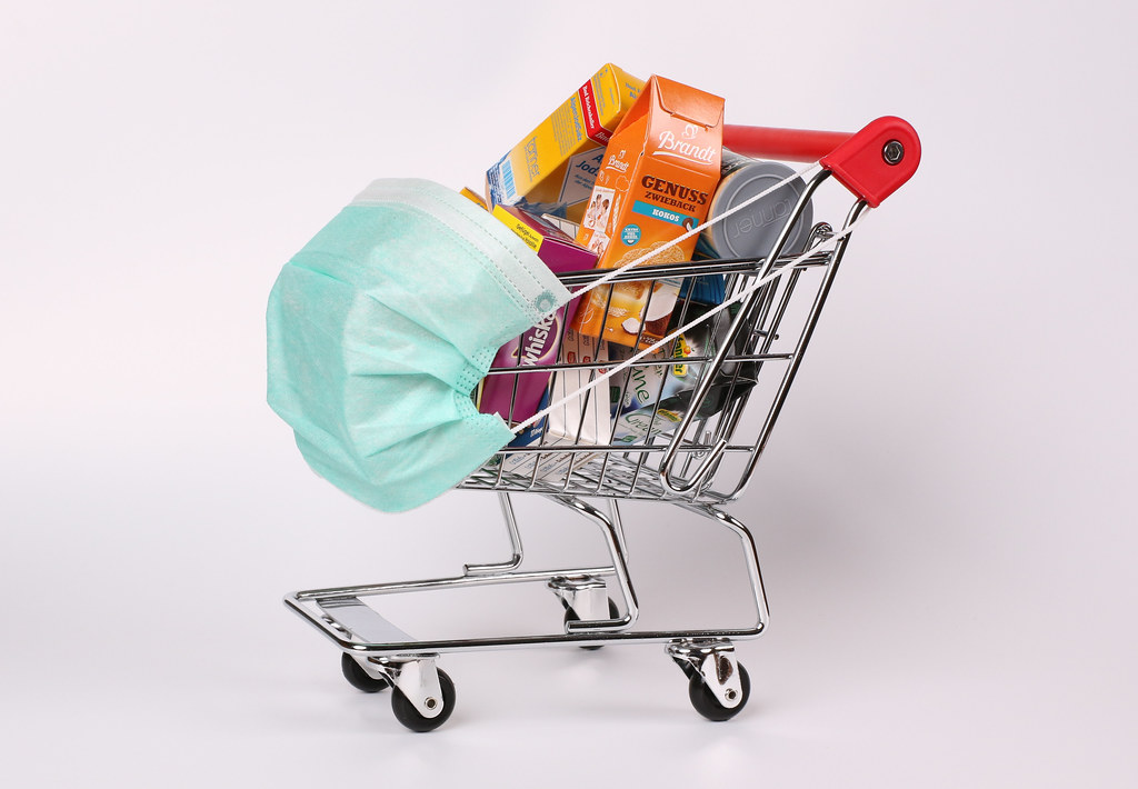 Red shopping cart and groceries with protective face mask corona virus or Covid-19 protection