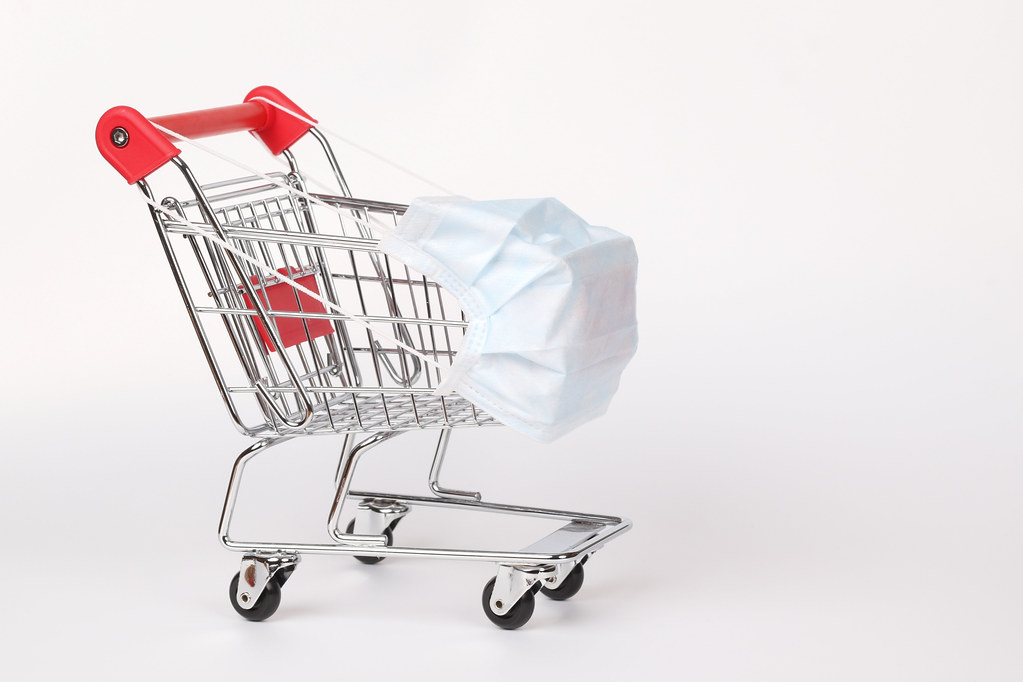 Red shopping cart with medical mask for virus protection on white background. Creative concept of healthcare and safe shopping on coronavirus quarantine