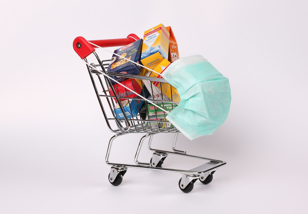 Shopping cart and groceries with protective face mask corona virus or Covid-19 protection