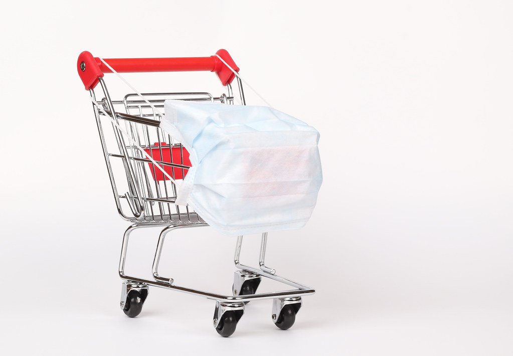 Shopping cart with medical mask for virus protection on white background. Creative concept of healthcare and safe shopping on coronavirus quarantine