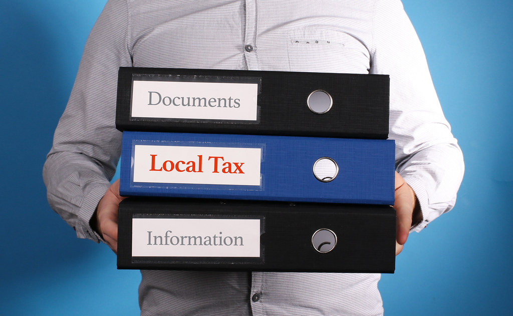 Local Tax – Businessman is carrying a stack of 3 file folders on blue background
