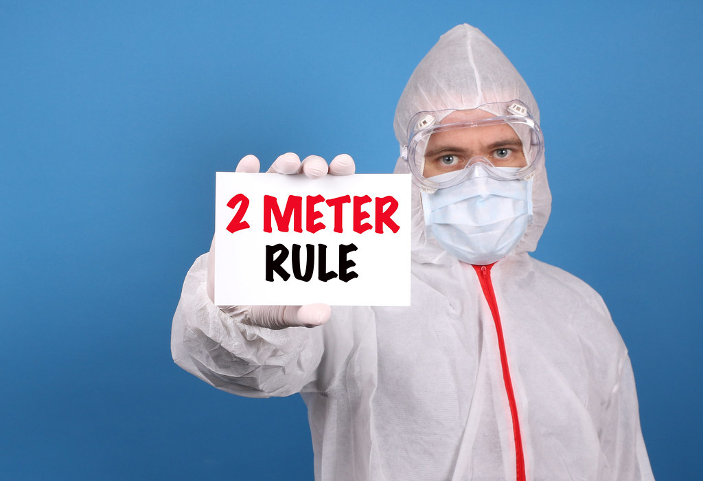 Medical doctor holding banner with 2 Meter Rule text, Isolated over blue background