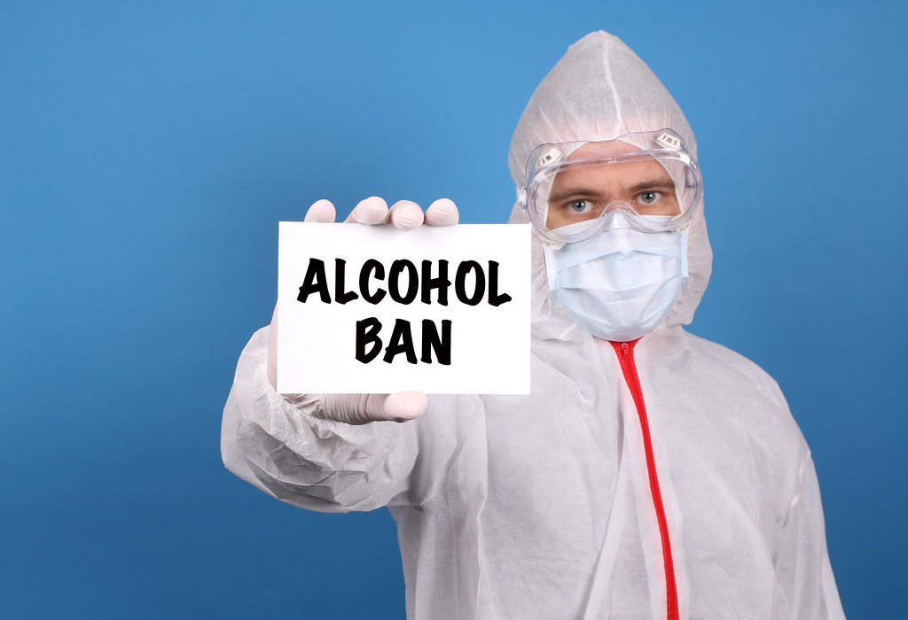 Medical doctor holding banner with Alcohol Ban text, Isolated over blue background