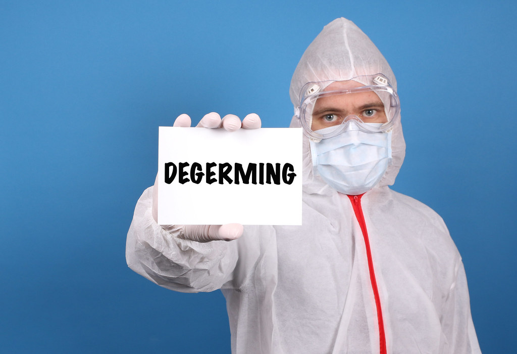 Medical doctor holding banner with Degerming text, Isolated over blue background