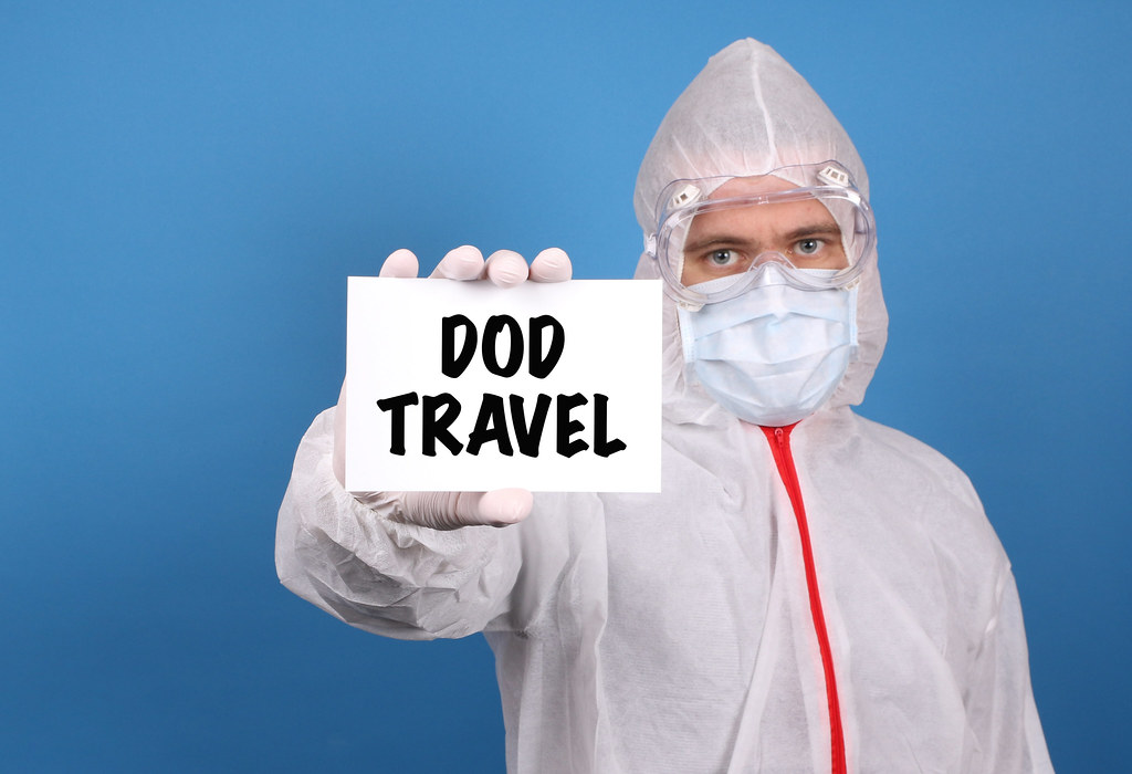Medical doctor holding banner with DoD Travel text, Isolated over blue background