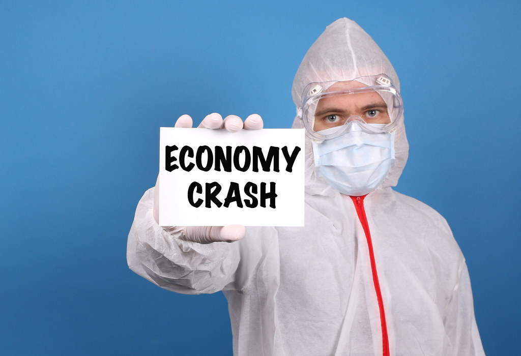 Medical doctor holding banner with Economy Crash text, Isolated over blue background