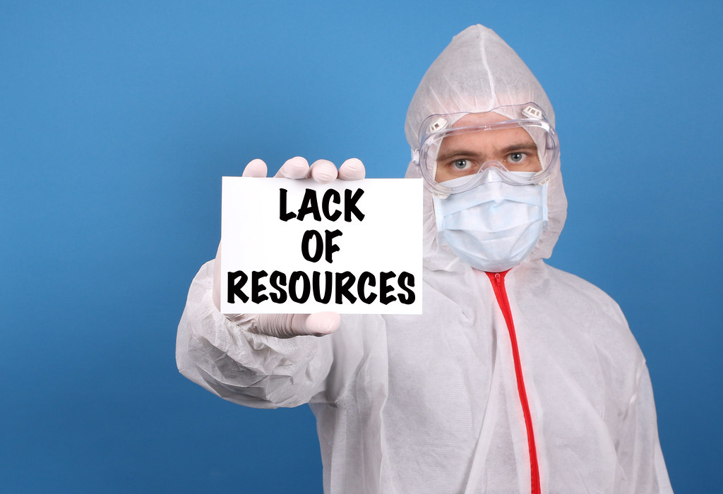 Medical doctor holding banner with Lack Of Resources text, Isolated over blue background