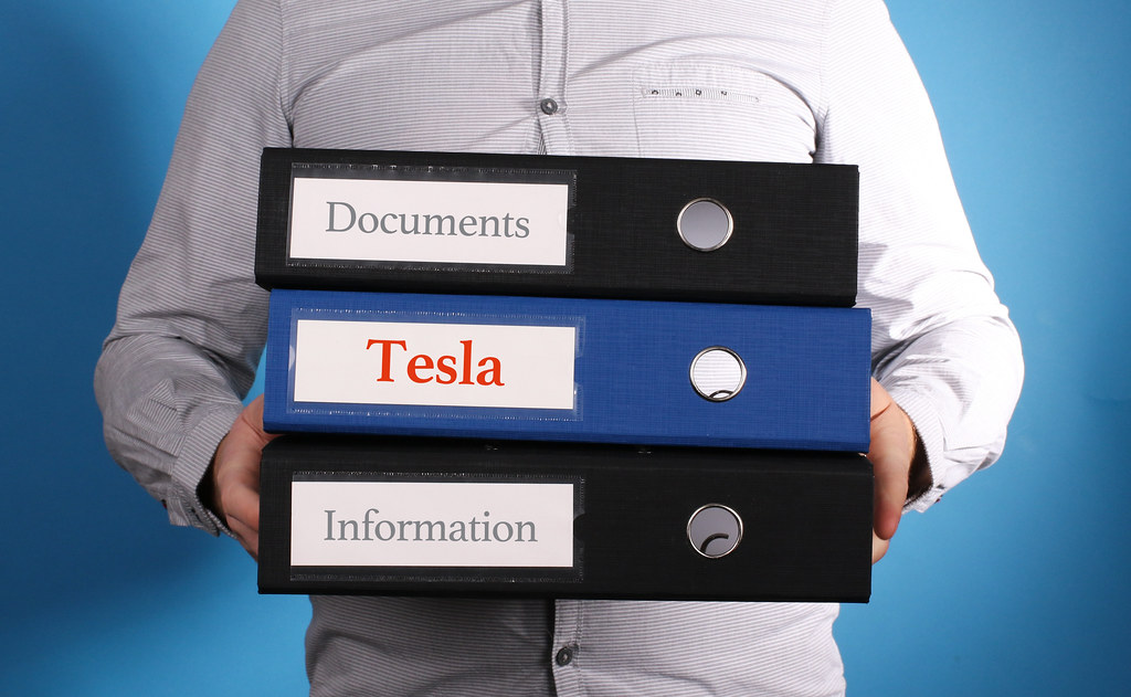 Tesla – Businessman is carrying a stack of 3 file folders on blue background