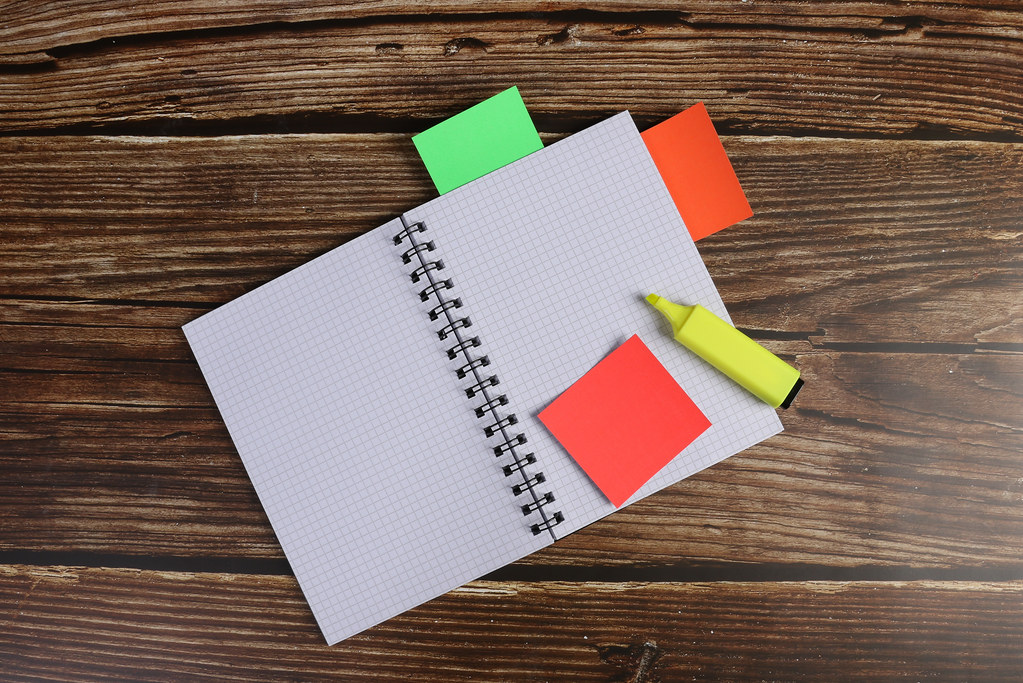 Empty notebook with colorful stickers on wooden table