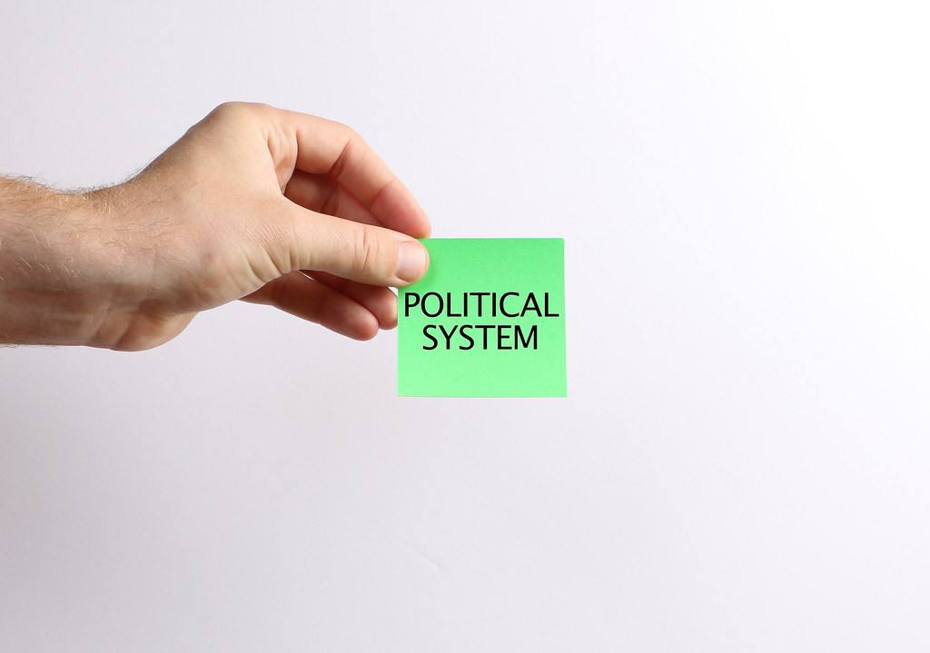 Hand holding green paper with Political System text