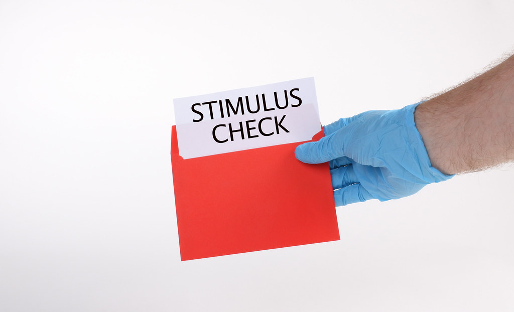 Hand in medical gloves holds red envelope with stimulus check
