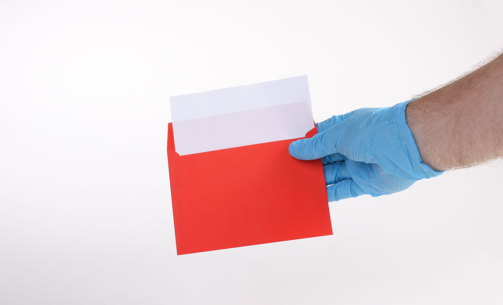 Hand in medical gloves holds red envelope
