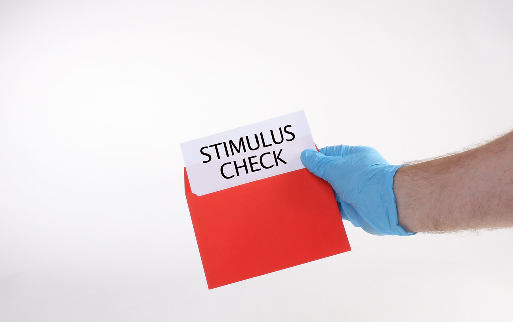 Hand in medical gloves opens a red envelope with Stimulus check