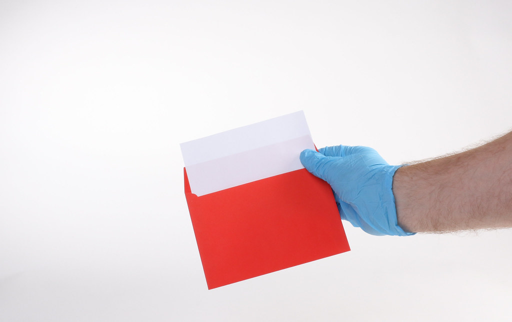 Hand in medical gloves opens a red envelope