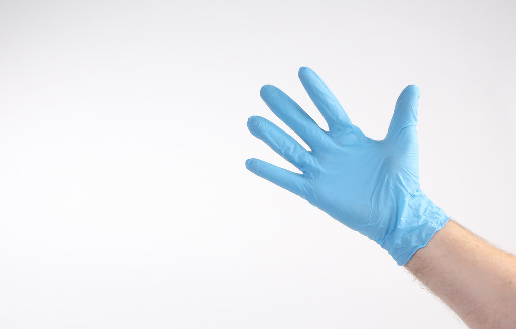 Hand with blue medical glove
