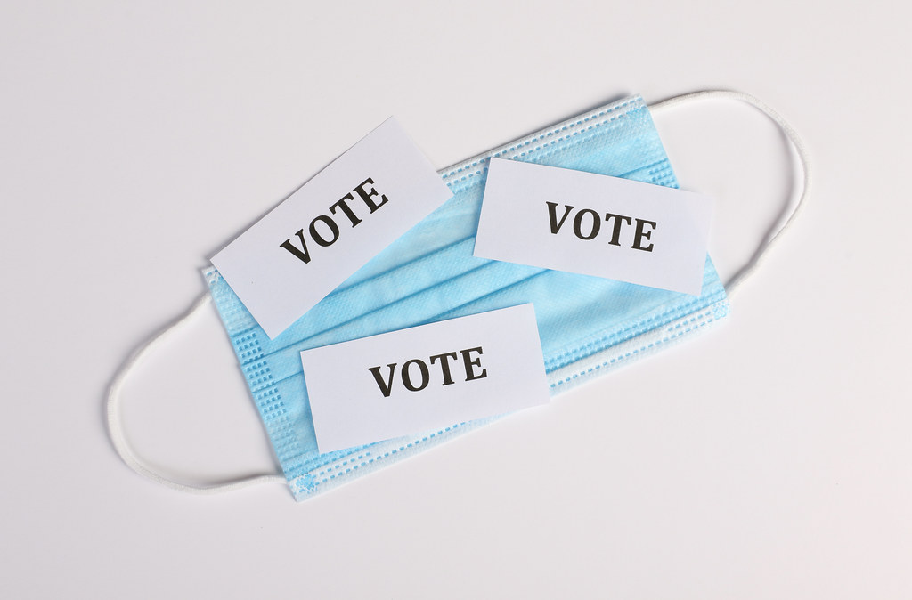 Medical face mask with small white papers with Vote text on it. Voting with mask concept