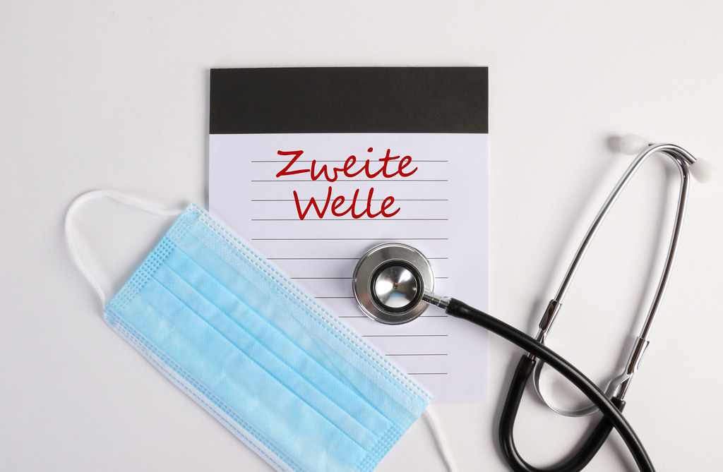 Notebook with stehoscope and face mask on white background with Zweite Welle text