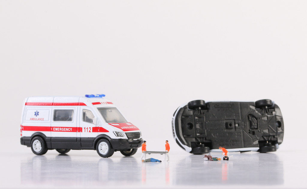 Ambulance crew helping unconscious and injured people on ground, first aid at car accident scene