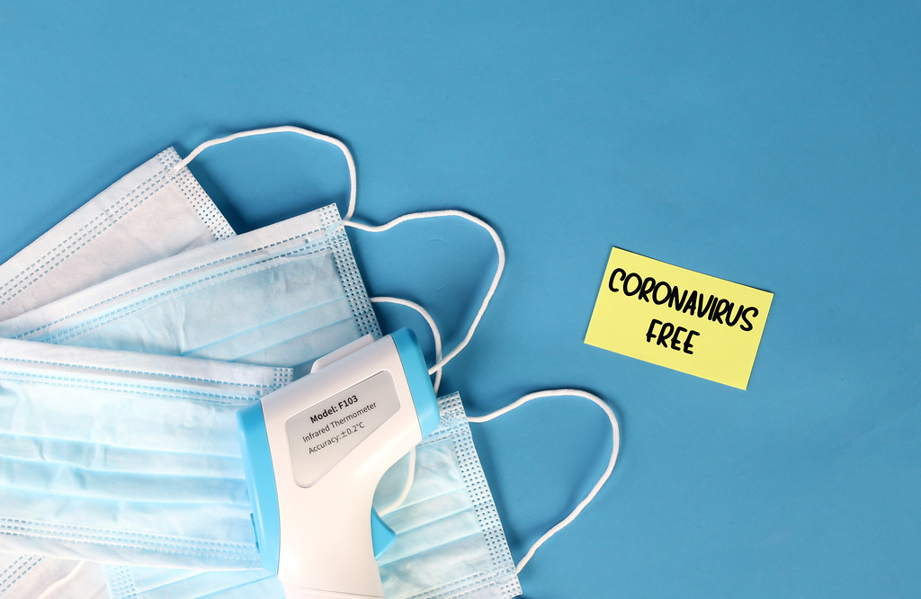 Coronavirus Free text written on yellow sticky note with infrared thermometer gun and surgical masks on blue background