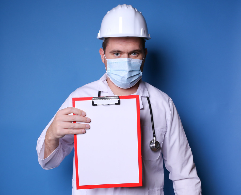 Doctor with hard hat and mask and stethoscope holding blank clipboard, blue background with copy space
