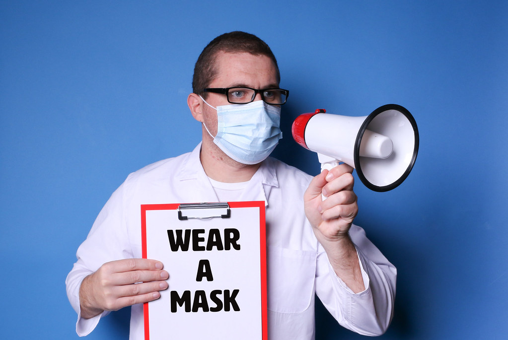 Doctor with mask and glasses, holding megaphone and clipboard with text Wear A Mask on blue background