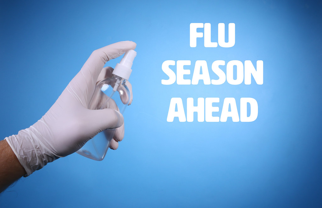 Flu Season Ahead text and hand with surgical gloves holding sanitize gel bottle on blue background