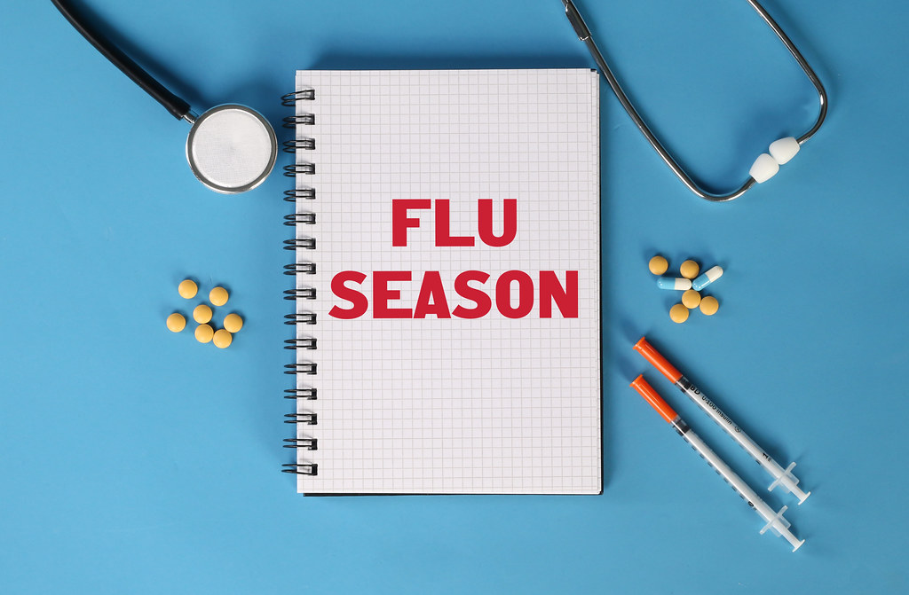 Flu Season red text written on spiral grid notepad with stethoscope, syringe and medicine pills on blue background