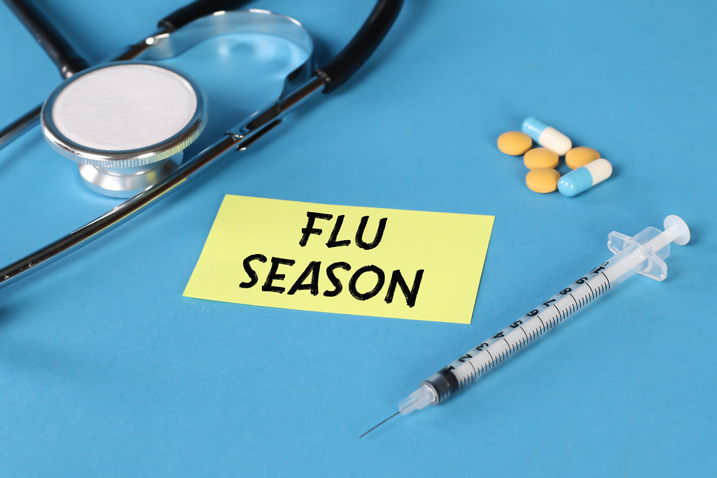 Flu Season text written on yellow note with pills, syringe and stethoscope on blue background