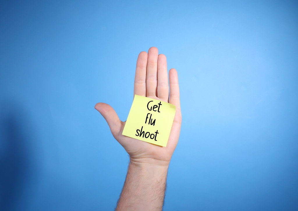 Get Flu Shoot text on yellow sticky note on palm of a man hand on blue background