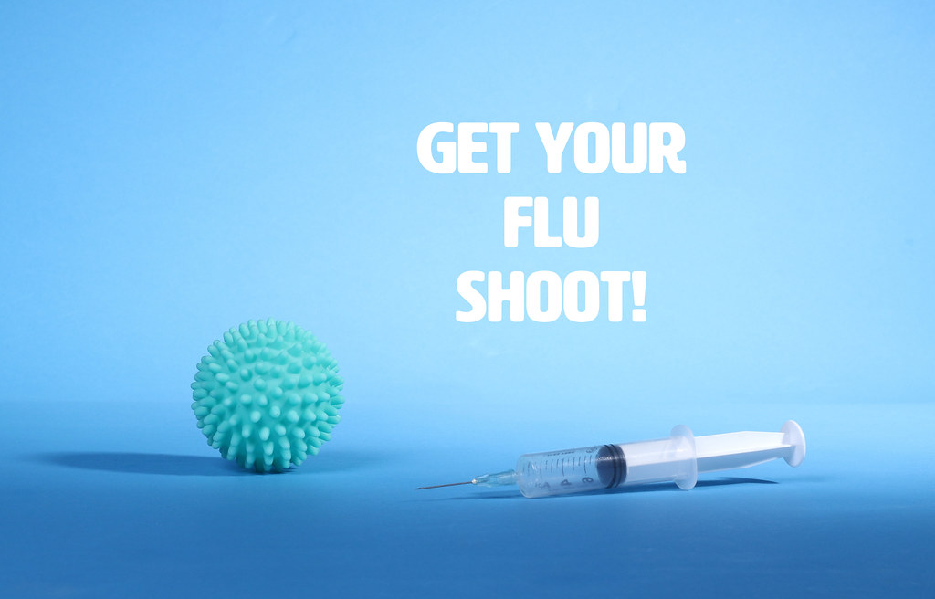 Get Your Flu Shoot text and Coronavirus with syringe on blue background