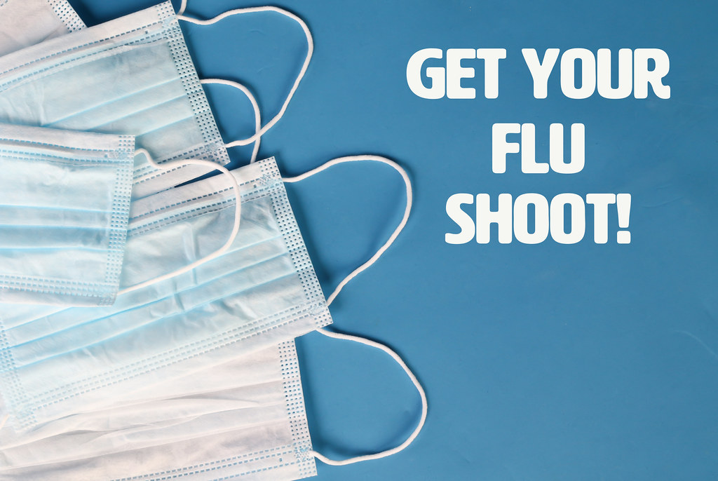 Get Your Flu Shoot text and surgical masks on blue background