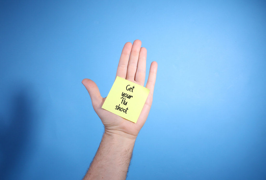 Get Your Flu Shoot text on sticky note on palm of a hand blue background