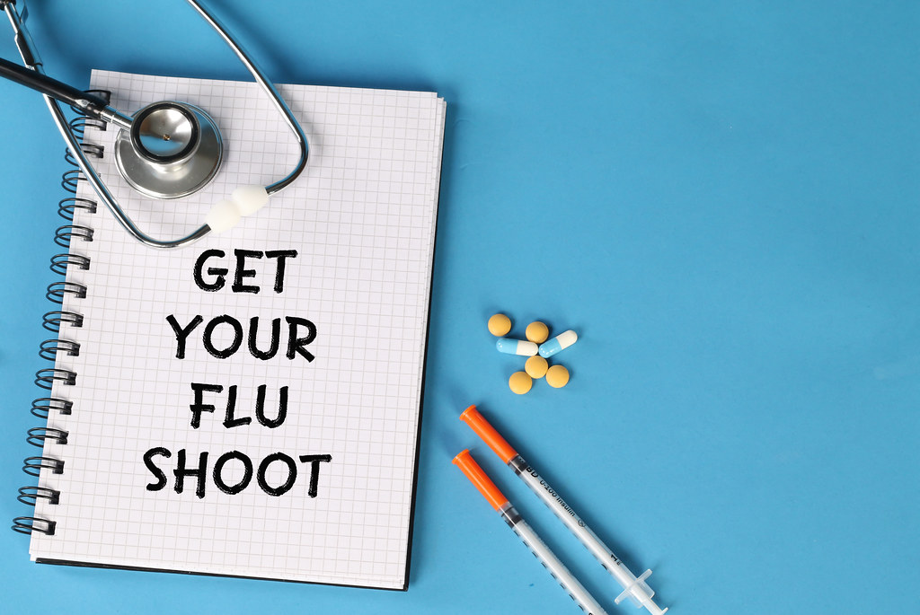 Get Your Flu Shoot text written on spiral grid notepad with stethoscope, syringe and pills on blue surface