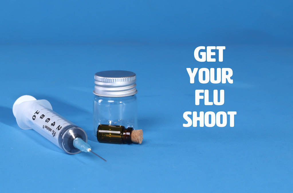 Get Your Flue Shoot text and syringe with glass bottles on blue background