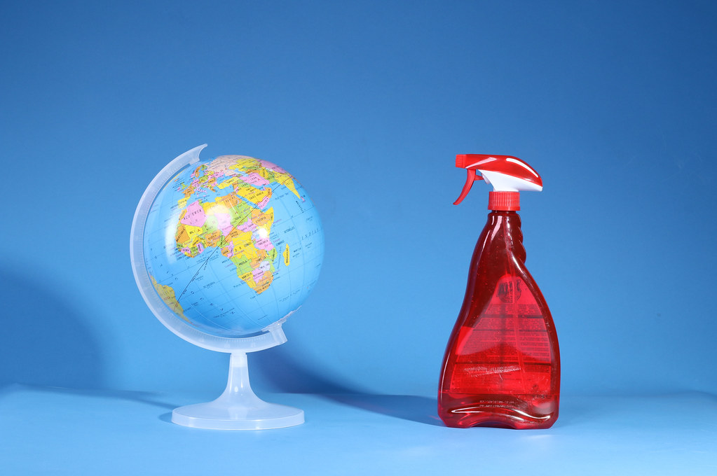 Globe and spray detergent on blue background. COVID-19 concept