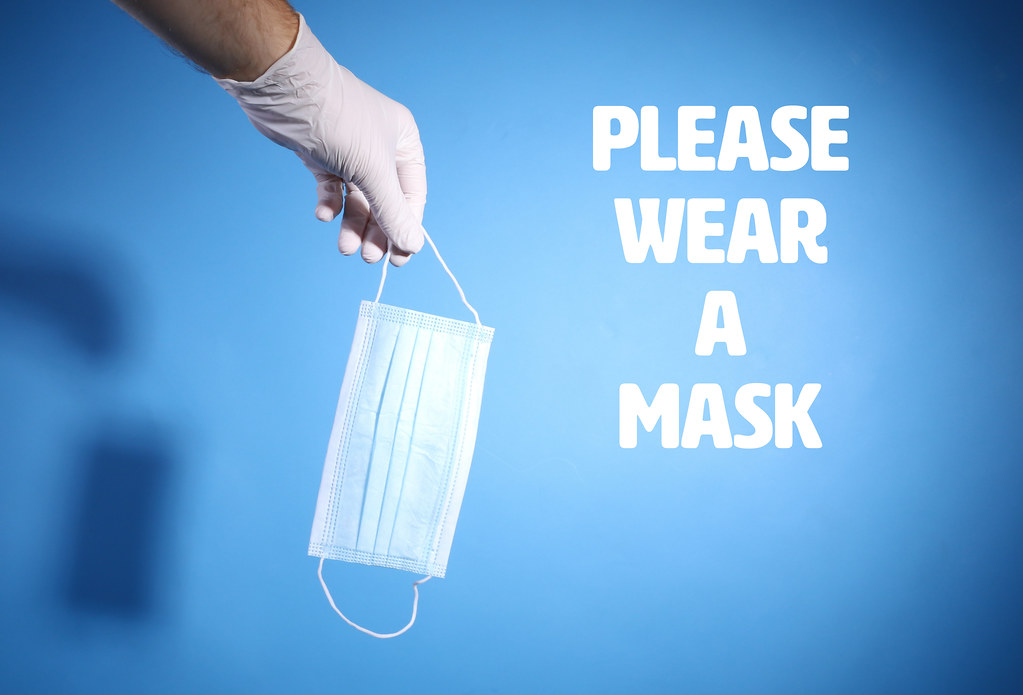 Hand with surgical latex mask holding 3-ply mask and text Please Wear A Mask on blue background