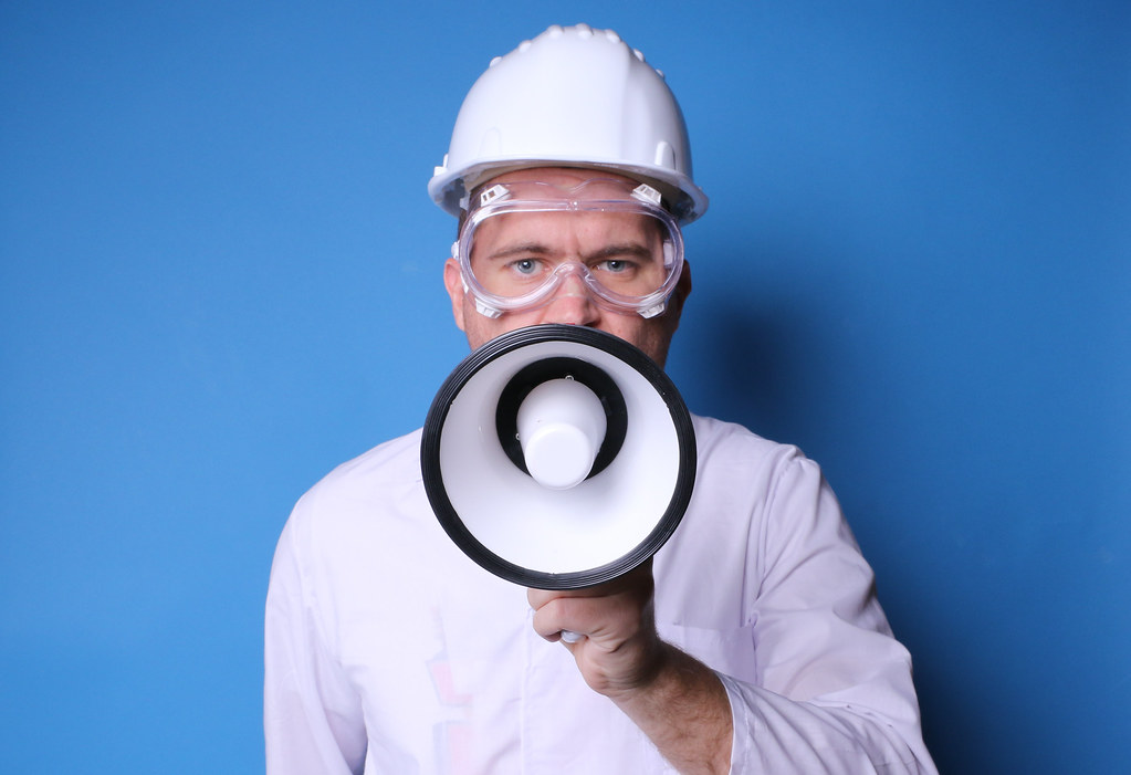 Man in white uniform with hard hat and safety glasses, holding megaphone and speaking, looking at camera, blue background