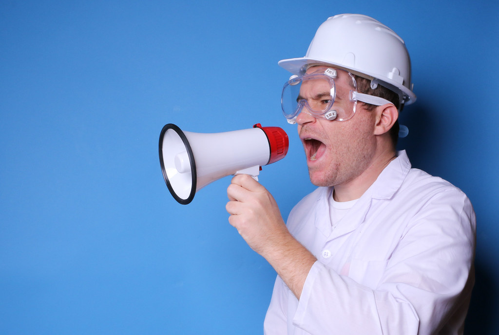 Man in white uniform with safety glasses and hard hat, holding megaphone and speaking, on blue background with copy space