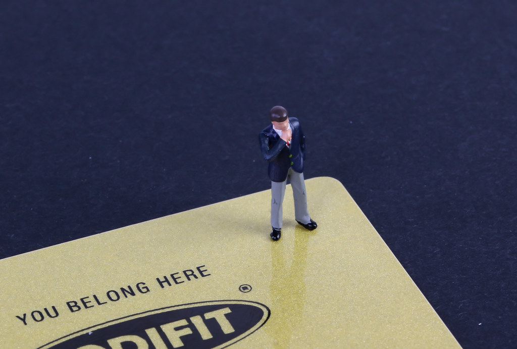 Miniature businessman on a yellow creditcard