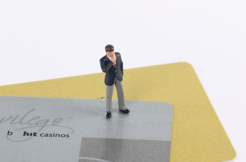 Miniature businessman on credit cards