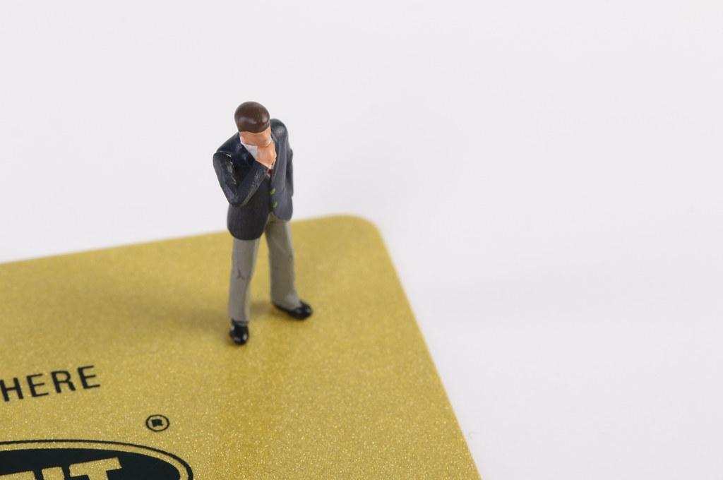 Miniature businessman standing on a creditcard