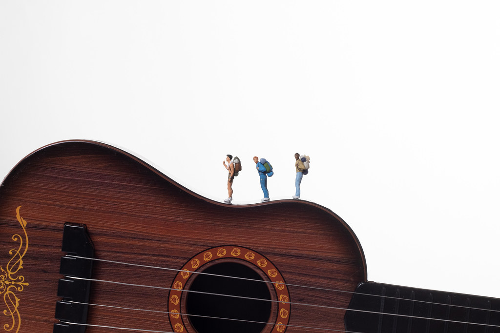 Miniature travelers on a acoustic guitar