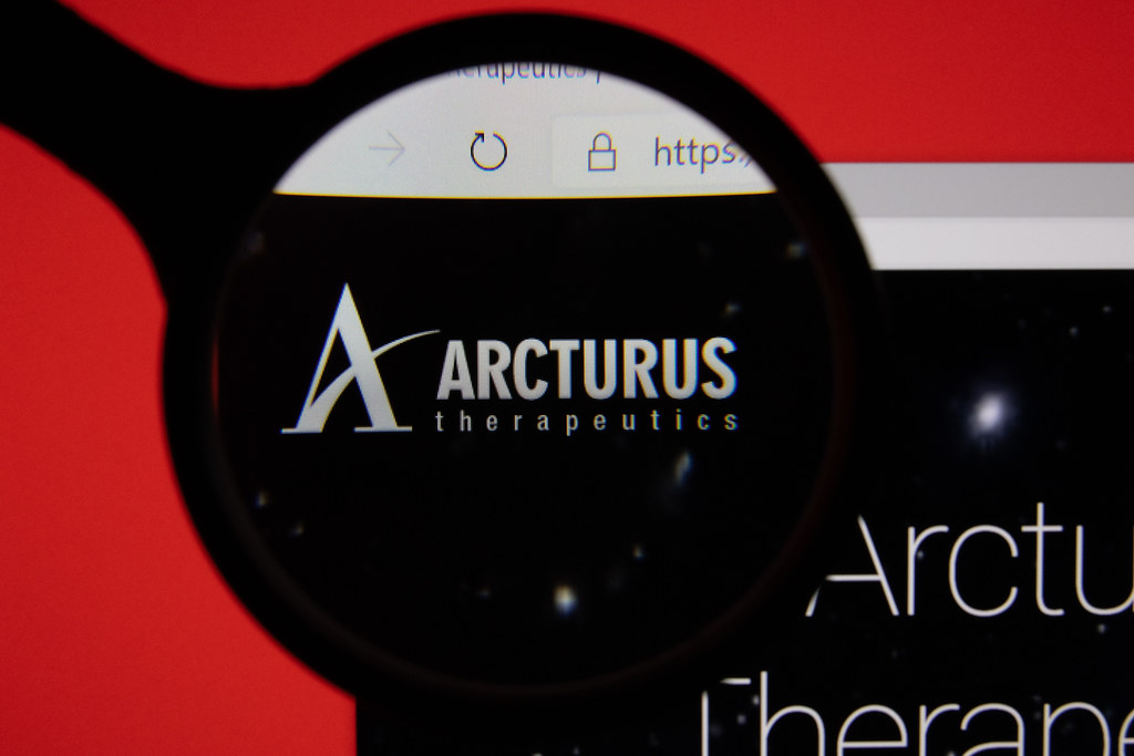 Arcturus Therapeutics company website page logo on laptop display with red background