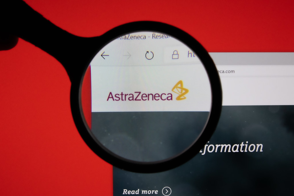 AstraZeneca company website page logo on laptop display with red background